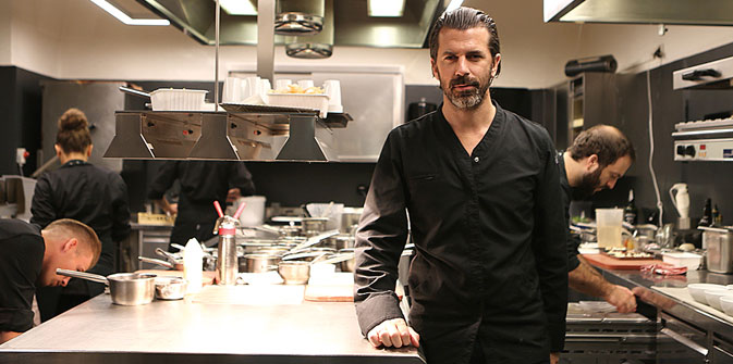 Andreas Caminada (7 Michelin Stars) standing in his restaurant kitchen